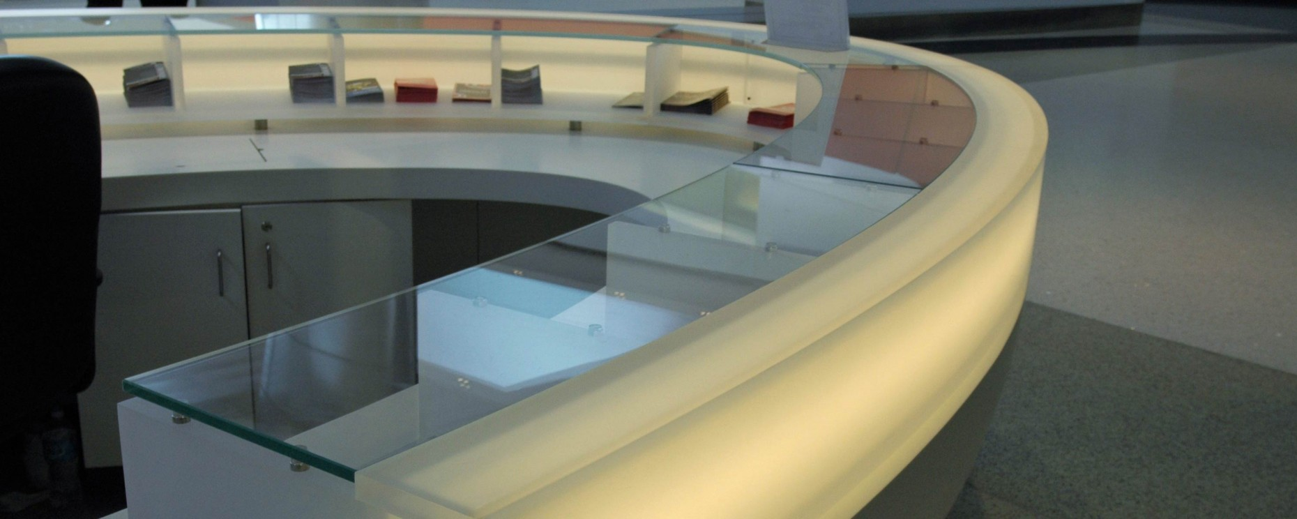 Thermoformed information desk fabricated with DuPont Corian®, 3form® and glass.
