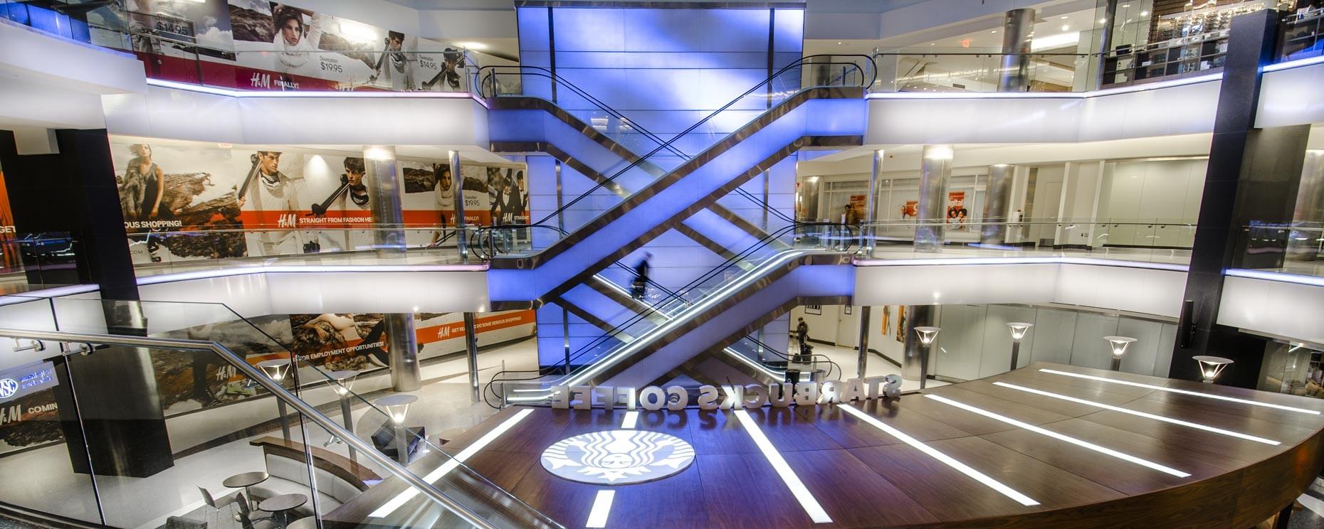 Translucent resin light walls, escalators, stair risers, Starbucks ® Coffee kiosk and public seating areas